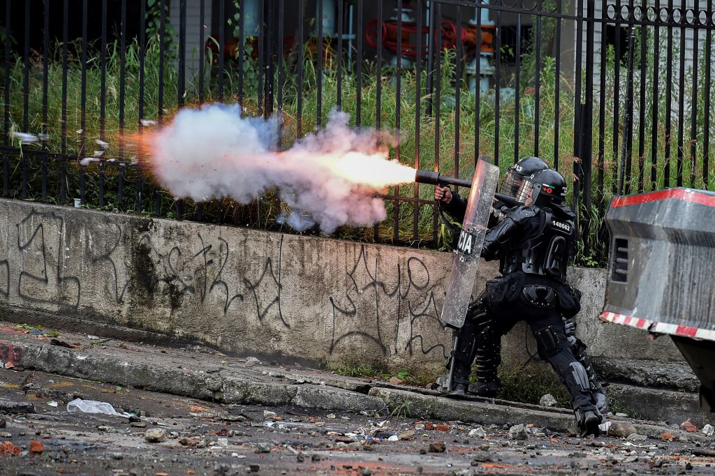 TOPSHOT - A riot police officer fires tear gas at demonstrators during  a protest against the government in Cali, Colombia, on May 10, 2021. - Faced with angry street protests and international criticism over his security forces' response, Colombia President Ivan Duque is coming across as erratic and out of touch with a country in crisis, analysts say. Since April 28, hundreds of thousands of people have vented their frustrations against the government after poverty and violence soared during the pandemic. (Photo by Luis ROBAYO / AFP) (Photo by LUIS ROBAYO/AFP via Getty Images)