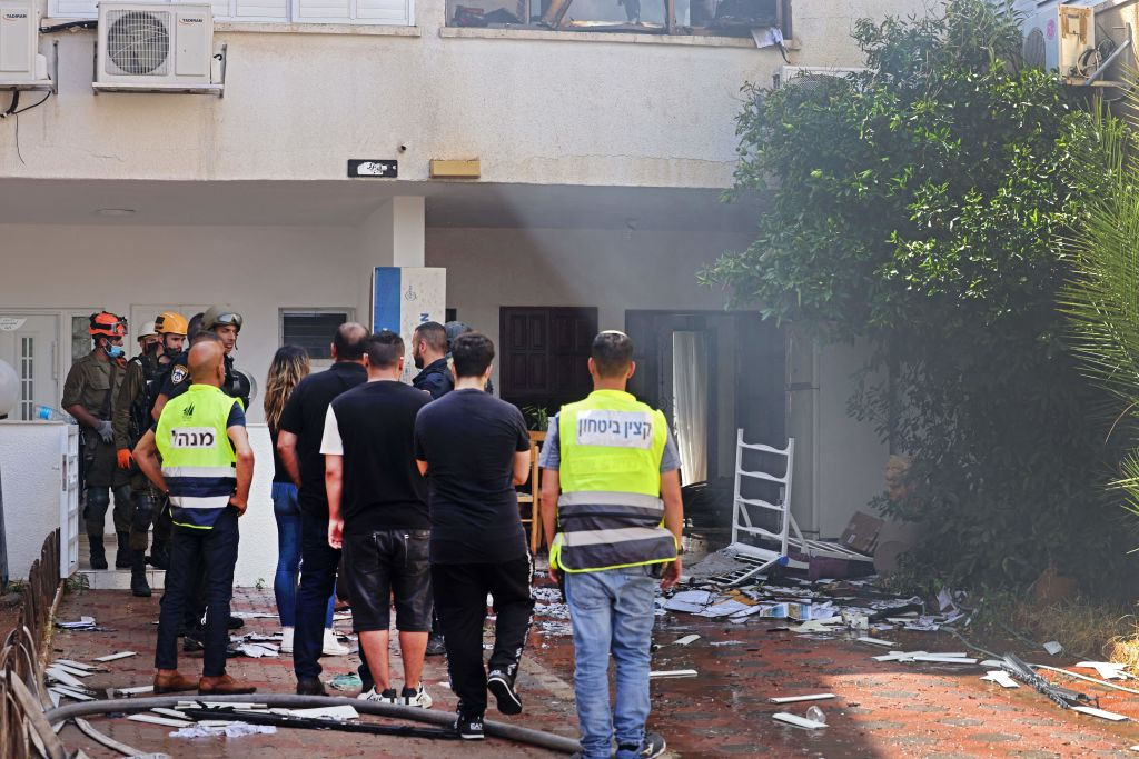 Israeli security forces gather outside a house hit by a rocket launched from the Gaza Strip, controlled by the Palestinian Hamas movement, into the southern Israeli city of Ashdod on May 11, 2021. - Rockets fired from Gaza killed two women in the southern Israeli city of Asheklon Tuesday, the Magen David Adom emergency service told AFP, after Palestinians militants unleashed a massive barrage. (Photo by Menahem KAHANA / AFP) (Photo by MENAHEM KAHANA/AFP via Getty Images)