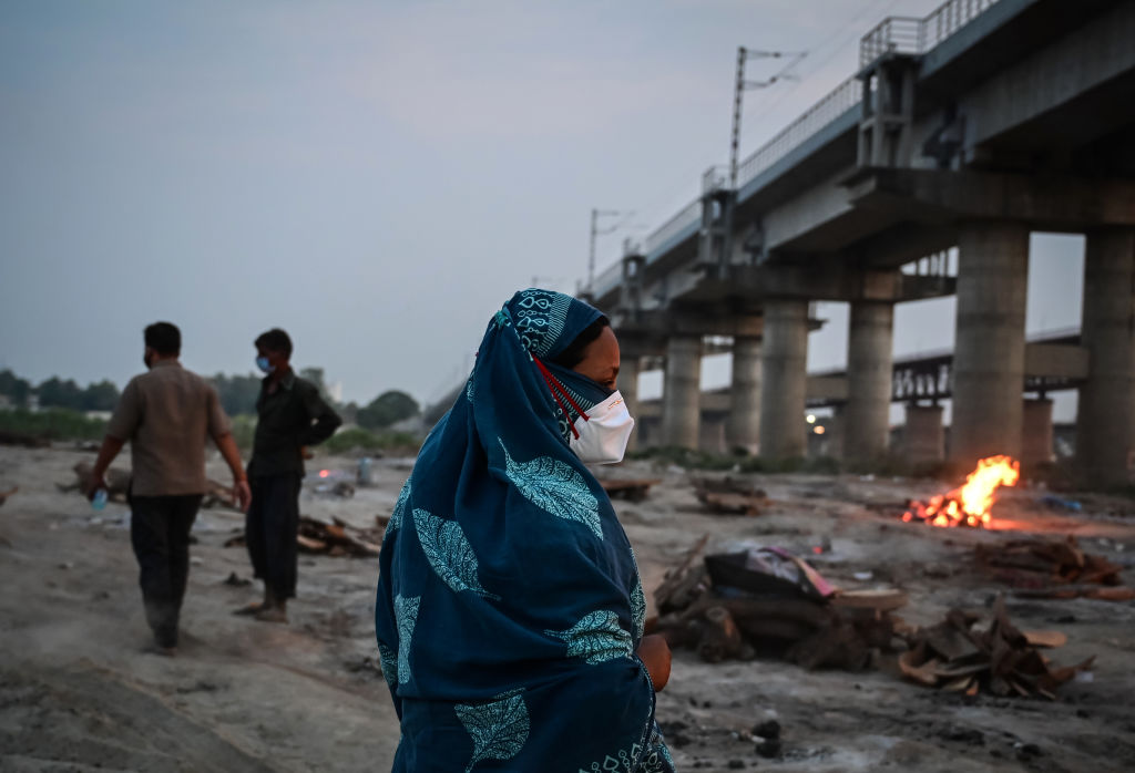 ALLAHABAD, INDIA - MAY 06: Relatives walk away from bodies of Covid-19 victims being cremated on the banks of the Ganges river May 06, 2021 in Allahabad, Uttar Pradesh, India. India broke a fresh record on Thursday with over 412,000 new cases of Covid-19 as the total number of those infected according to Health Ministry data neared 20 million. The real figure could be up to ten times higher, many health experts say, due to a lack of widespread testing or reporting, and only patients who succumbed in hospitals being counted. Hospitals have begun turning away people suffering from Covid-19, having run out of space for the crushing number of people seeking help. (Photo by Ritesh Shukla/Getty Images)