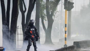 A riot police officer walks through a cloud of tear gas amid clashes with demonstrators during a protest against the government of Colombian President Ivan Duque in Bogota on June 9, (Photo by Juan BARRETO / AFP) (Photo by JUAN BARRETO/AFP via Getty Images)