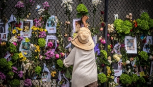 TOPSHOT - A woman adds flowers to a memorial featuring photos of some of those lost in the partially collapsed 12-story Champlain Towers South building on June 28, 2021 in Surfside, Florida. - Questions mounted Monday about how a residential building in the Miami area could have collapsed so quickly and violently last week, as the death toll rose to 11 with 150 still unaccounted for, and desperate families feared the worst. (Photo by Giorgio Viera / AFP) (Photo by GIORGIO VIERA/AFP via Getty Images)