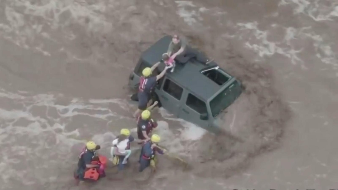 Rescatan a una familia de un auto en las inundaciones