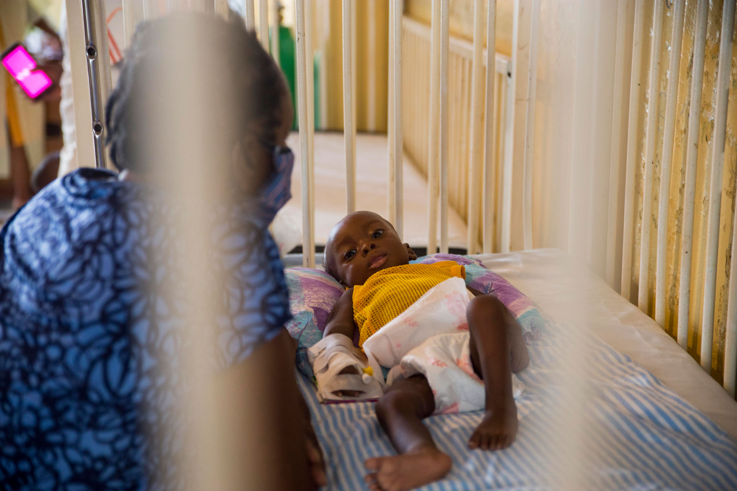 Marie Rose Emile watches over her 6-month-old grandson Jonise as he is treated for malnutrition at the HospitalofImmaculate Conception, in Les Cayes, Haiti, Wednesday, May 26, 2021. UNICEF's regional director for Latin America and the Caribbean visited the southern seaport amid concerns over an increase in malnutrition and a drop in childhood immunizations that officials blame on the coronavirus pandemic. (AP Photo/Joseph Odelyn)