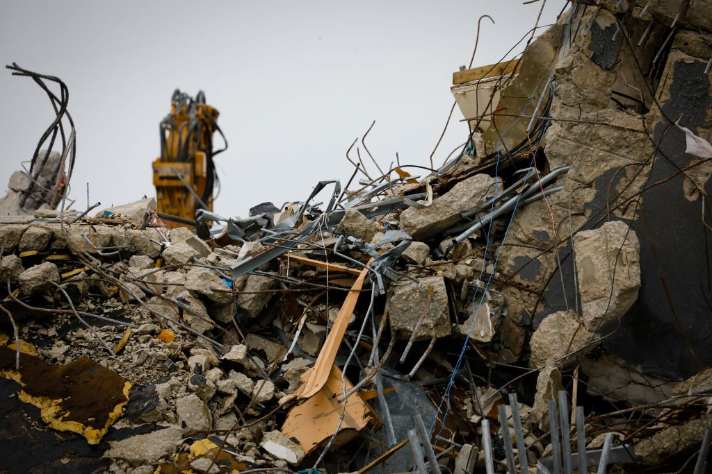 The rubble of the collapsed building Champlain tower is seen in Surfside, Florida on July 6, 2021. - Rescuers raced to search the site of a deadly condo tower collapse in Florida as Tropical Storm Elsa barreled closer, threatening the operation with torrential downpours and strong winds. The death toll from the June 24 disaster in Surfside rose overnight to 32 as search teams found four more bodies in the rubble, Miami-Dade County Mayor Daniella Levine Cava told reporters. (Photo by Eva Marie UZCATEGUI / AFP) (Photo by EVA MARIE UZCATEGUI/AFP via Getty Images)