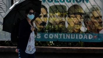A woman wearing a face mask walks near a poster with images of Cuban revolutionary (L-R) Cuban national hero Jose Marti, Cuban late leader Fidel Castro, the Former First Secretary of the Communist Party Raul Castro and Cuban President Miguel Diaz-Canel, in Havana, on June 3 2021. - Out of the official scene for a month and a half, Cuban leader Raul Castro turns 90 on Thursday, after leaving the leadership of the ruling Communist Party on April 19, his last post. However, his image continues to be a daily sight in the streets of Havana and the official government recalled the date through all its channels. (Photo by YAMIL LAGE / AFP) (Photo by YAMIL LAGE/AFP via Getty Images)