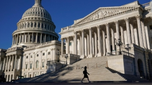 A woman walks past the U.S. Senate and Capitol dome on Capitol Hill in Washington, Thursday, Sept. 30, 2021. Congress is moving to avert one crisis while putting off another with the Senate poised to approve legislation that would fund the federal government into early December. (AP Photo/Patrick Semansky)